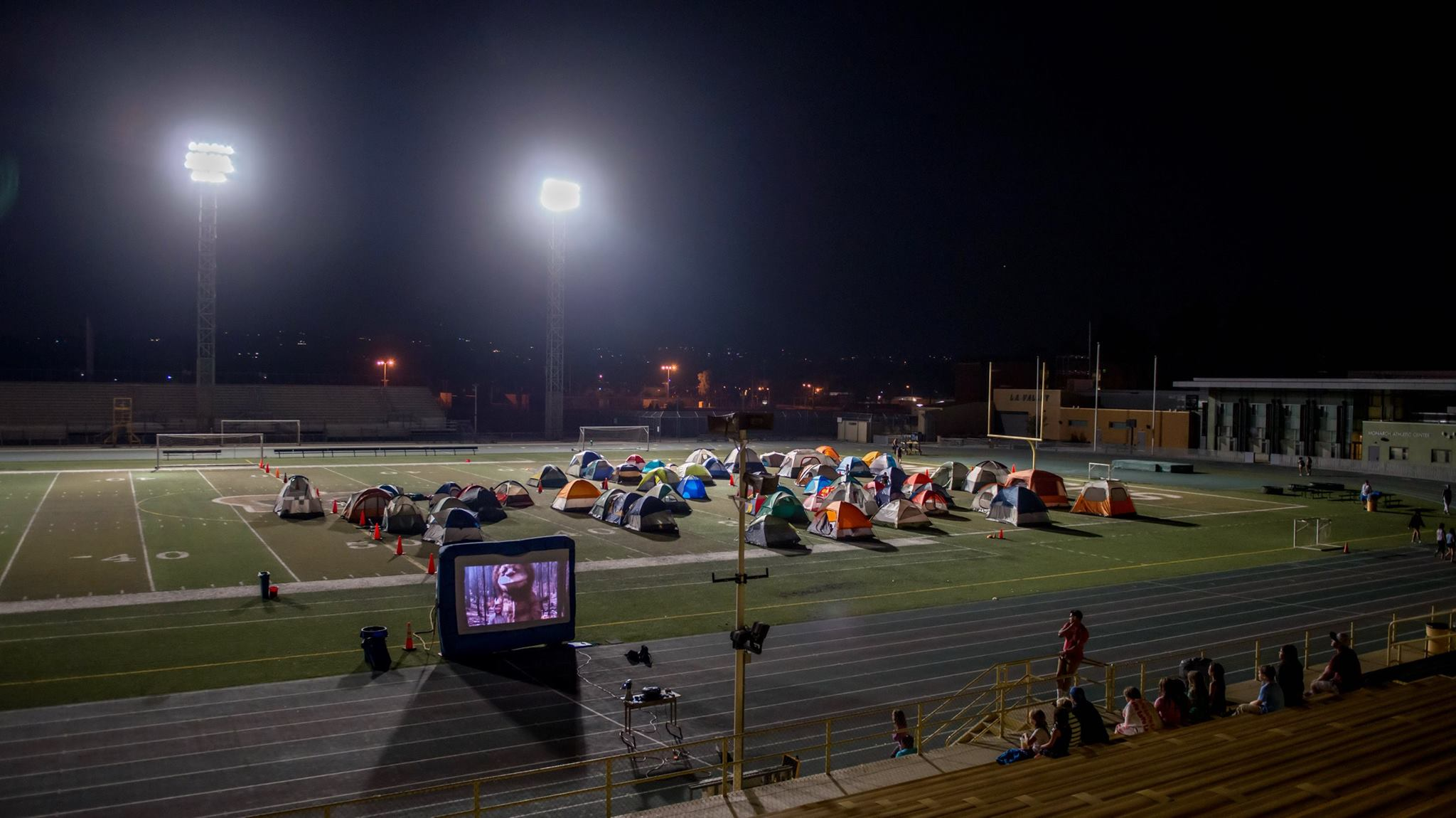 https://monarchcamps.com/wp-content/uploads/2018/01/monarch-camps-sleepover-sleepaway-camp-night-watching-movie-on-inflatable-rental-movie-projector-screen-at-los-angeles-valley-college-football-field.jpg